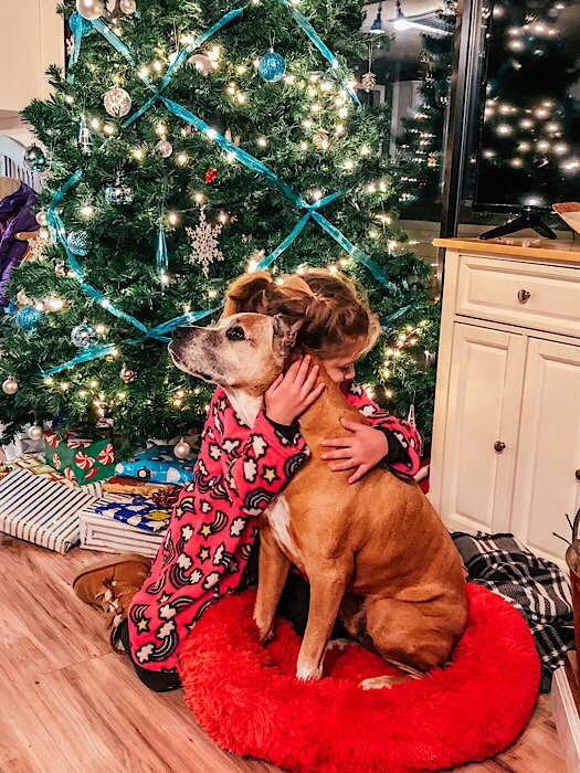 Girl hugging dog in front of Christmas tree